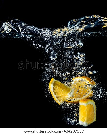 Orange slices falling into the water close-up, macro, splash, bubbles, black background - stock photo