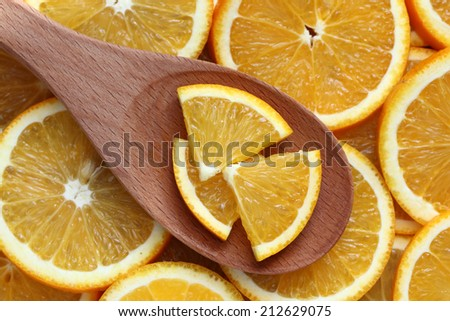 Orange slices in a wooden spoon on orange slices background. Close-up.