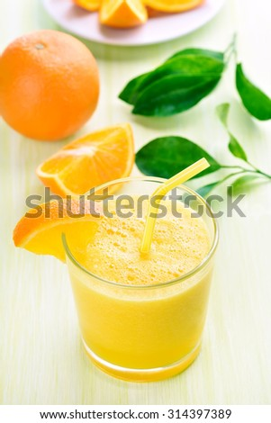 Orange smoothie in glass and slices - stock photo