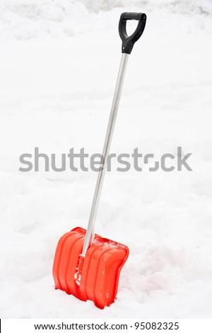 Orange snow shovel stick in snowdrift. - stock photo
