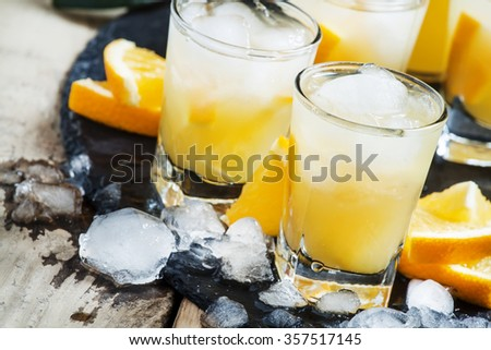 Orange soft drink with juice, vodka and ice, selective focus - stock photo