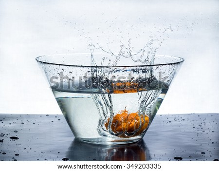 Orange splashes water in a big bowl on a black table - stock photo