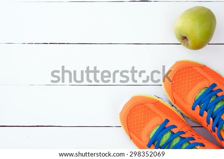 Orange sport shoes sneakers and apple on white wooden background. Top view sport equipment.