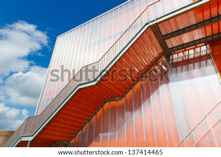 Orange stairs on the outside of modern building materials - stock photo