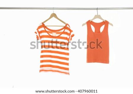 Orange striped,t-shirt hanging on wooden hangers   - stock photo