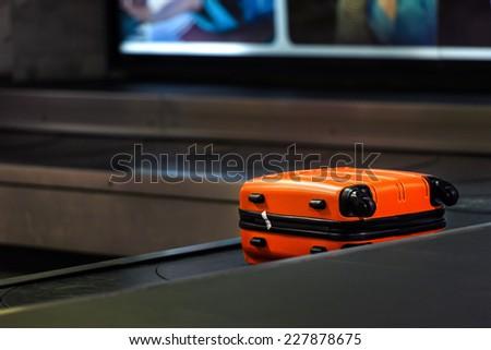 Orange suitcase waiting to be picked up - stock photo