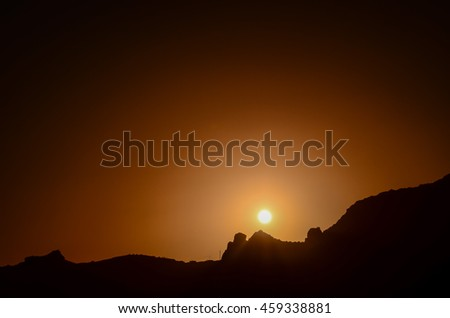 Orange Sun Setting Behind the Mountains