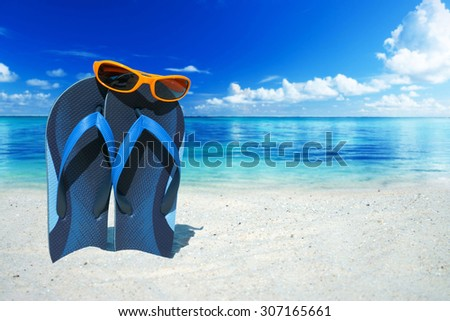 Orange sunglasses and blue flip flops on the beach in the summer