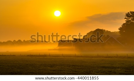 Orange sunrise over misty dutch countryside with barns and tractor in Twente, Netherlands - stock photo