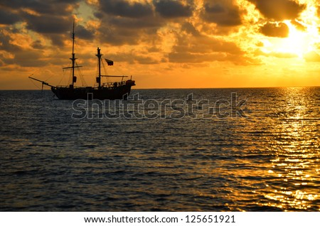 Orange sunrise with pirate ship on Caribbean Sea in San Andres, Colombia