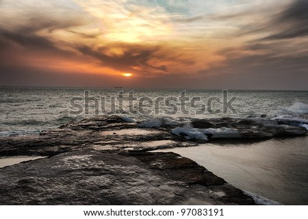 Orange sunset behind a bank of cloud on the horizon over a rippled ocean with low surf breaking over flat rocks in the foreground - stock photo