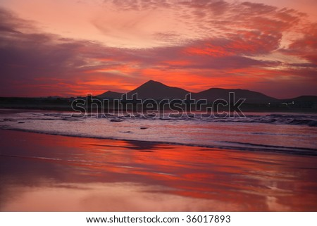 orange sunset in playa Famara, Lanzarote - stock photo