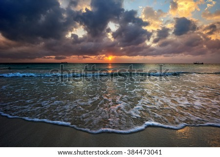 Orange sunset in the center opposing gray skies and dark sea - stock photo