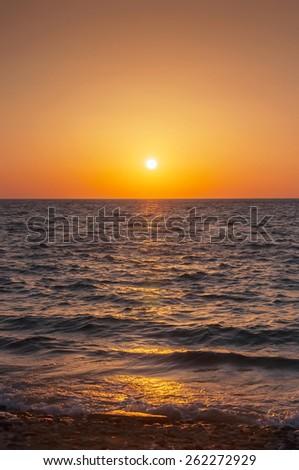 Orange sunset on the sea with the sun. Mykonos. Greece. - stock photo