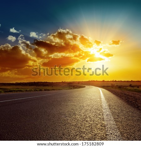 orange sunset over asphalt road - stock photo