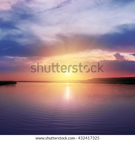 orange sunset over river in purple colors around - stock photo
