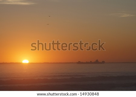 Orange sunset over the ocean with a boat as silhouette