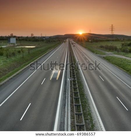 Orange sunset over the two-lane road. A speeding car. Suburbs of Krakow. - stock photo