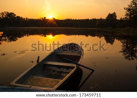 orange sunset sunrise lake boat and trees - stock photo