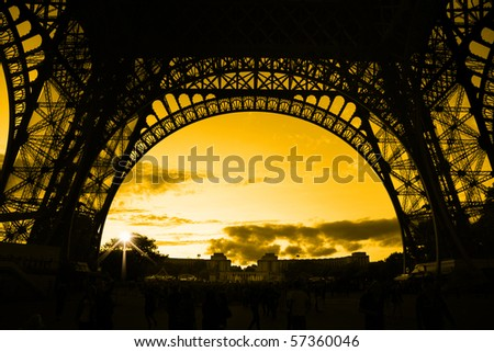 orange sunset under Eiffel Tower arches - stock photo