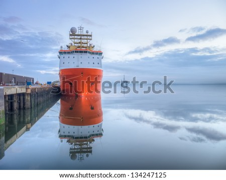 Orange supply vessel alongside of a quay with oil rig at sea and clouds reflected from water surface before sunrise - stock photo