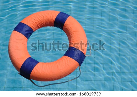 Orange swim ring with deep blue trim floating on water. - stock photo