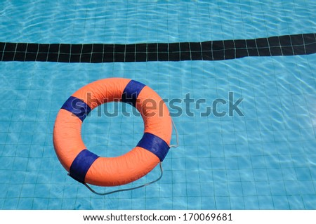 Orange swim ring with deep blue trim floating on water  - stock photo