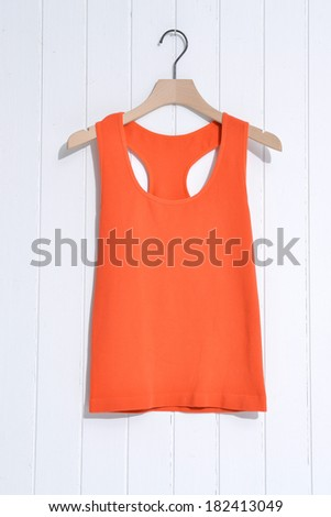 Orange t-shirt on wooden hangers-wooden background  - stock photo