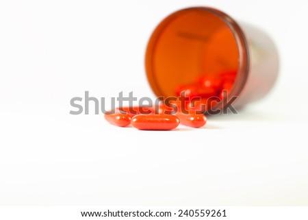 Orange tablet and medicine brown bottle - stock photo