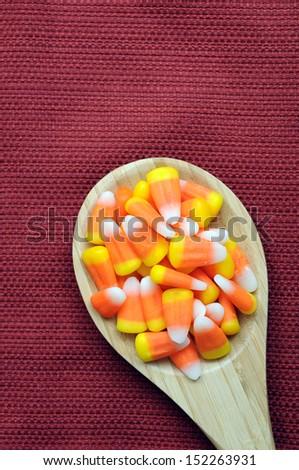 orange teeth candies in wooden spoon on table  - stock photo