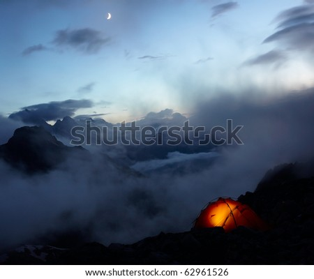 Orange tene in mountains and moon on the sky - stock photo