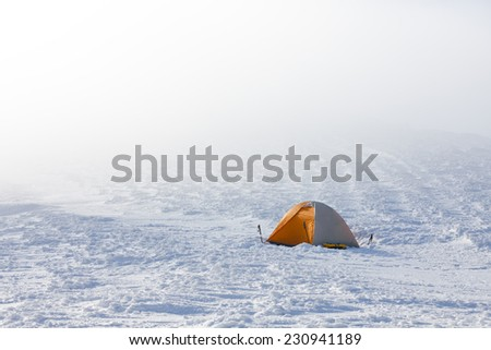 Orange tent in winter mountains on sunny day - stock photo