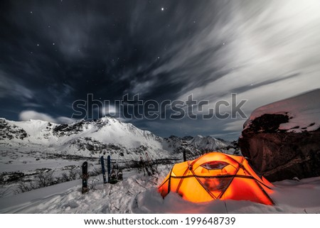 Orange tent on snow in mountains at night - stock photo