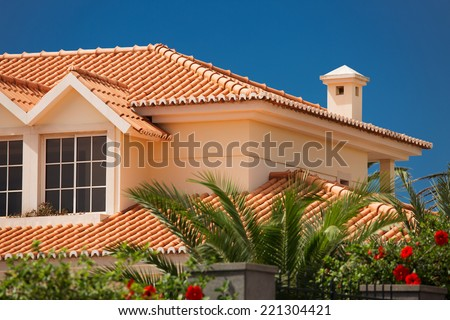 Orange tiled roof of a large house - stock photo