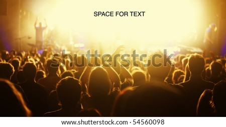 Orange-toned image of audience at live concert cheering with bright light at stage area as free space for text. - stock photo