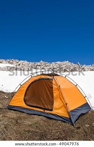 orange touristic tent on a snow - stock photo