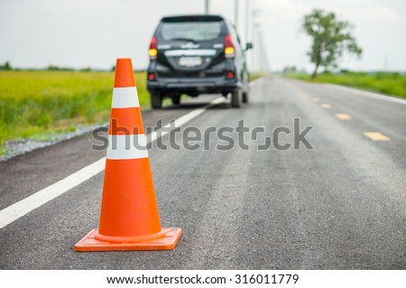 Orange traffic cone on country road. It is used for warning to broken down car on country road, Thailand. - stock photo