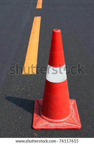 Orange traffic cone on road - stock photo