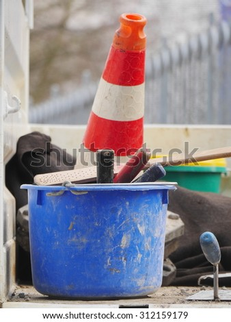 Orange traffic cone on road with bucket and tools - stock photo