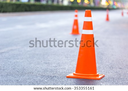 orange traffic cone on the road - stock photo