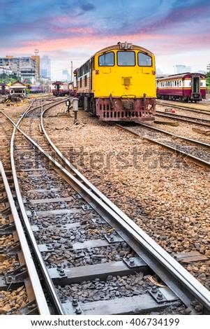 orange train diesel locomotive at dusk on bangkok railway station , thailand - stock photo