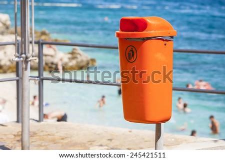 Orange trash bin near the sea beach. Littering the beach and the sea. - stock photo