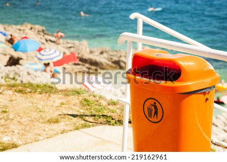Orange trash can near the sea beach. Littering the beach and the sea. - stock photo