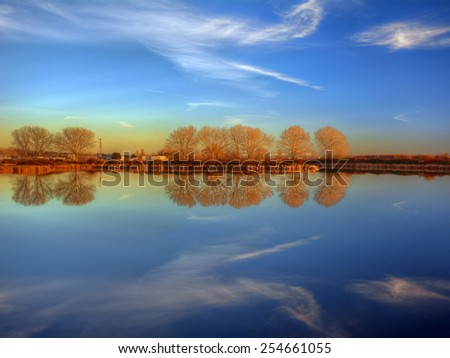 Orange trees on the horizon along a calm lake - stock photo