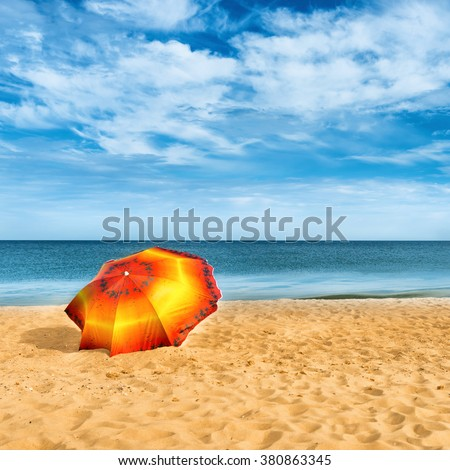 Orange umbrella on golden sand beach in a sunny day, blue sea in background - stock photo