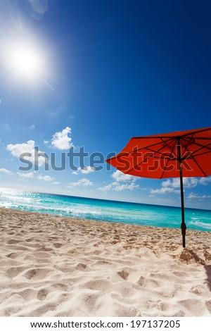 Orange umbrella on the white sand beach and beautiful sky - stock photo