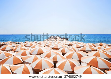 orange umbrellas on the beach, as a sign of vacation