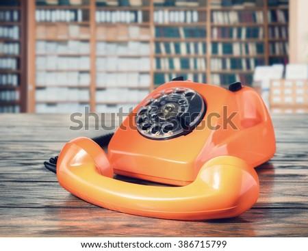 Orange vintage phone in the office - stock photo