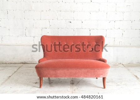 Orange vintage sofa on white wall.