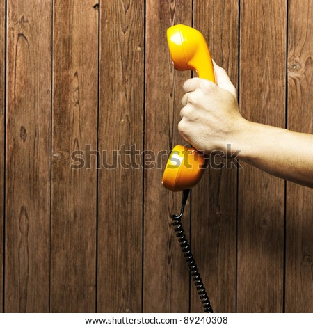 orange vintage telephone against a wooden wall